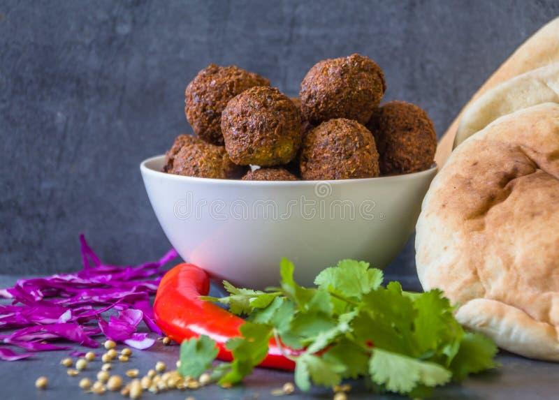 Tradycyjne domowej roboty chickpea Falafel piłki w pucharze z kolenderami opuszczają & ziarna, czerwony pieprz & kapusta, pitta c zdjęcia stock