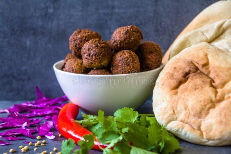 Tradycyjne domowej roboty chickpea Falafel piłki w pucharze z kolenderami opuszczają & ziarna, czerwony pieprz & kapusta, pitta c zdjęcia royalty free