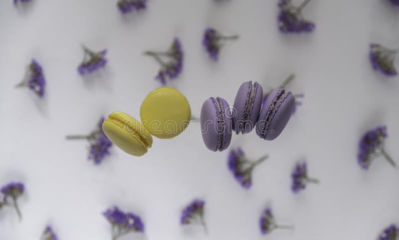 Tradycyjne Francuskie purpury, żółci macaroons na kwiatu tle fotografia stock