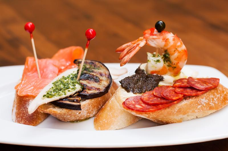Tradycyjne Hiszpańskie kuchni przekąski Tapas baguette canape z chorizo kiełbasami, czarne oliwki, piec na grillu oberżyna, łosoś obraz royalty free