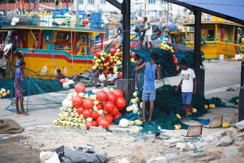 Tradycyjne Sri Lanka łodzie rybackie w Mirissa schronieniu Rybacy rozplątują sieci rybackie zdjęcie stock