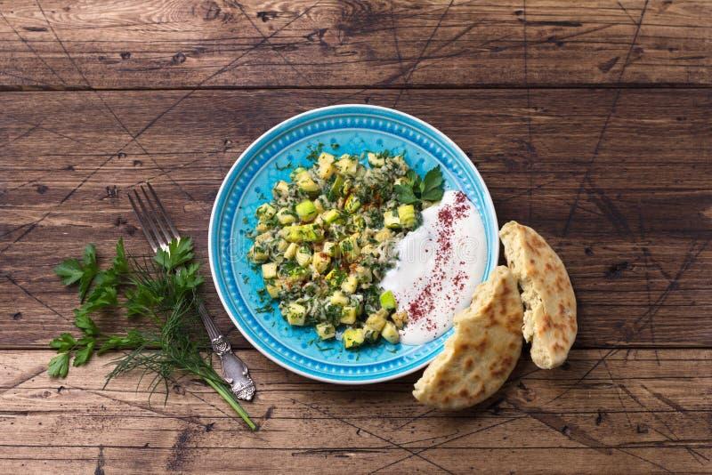 Tradycyjne tureckie jaja smażone z cukiniami i zioÅ'ami z sosem czosnkowym jogurtowym i Å›wieżymi tortillami na drewnianym stole zdjęcie stock