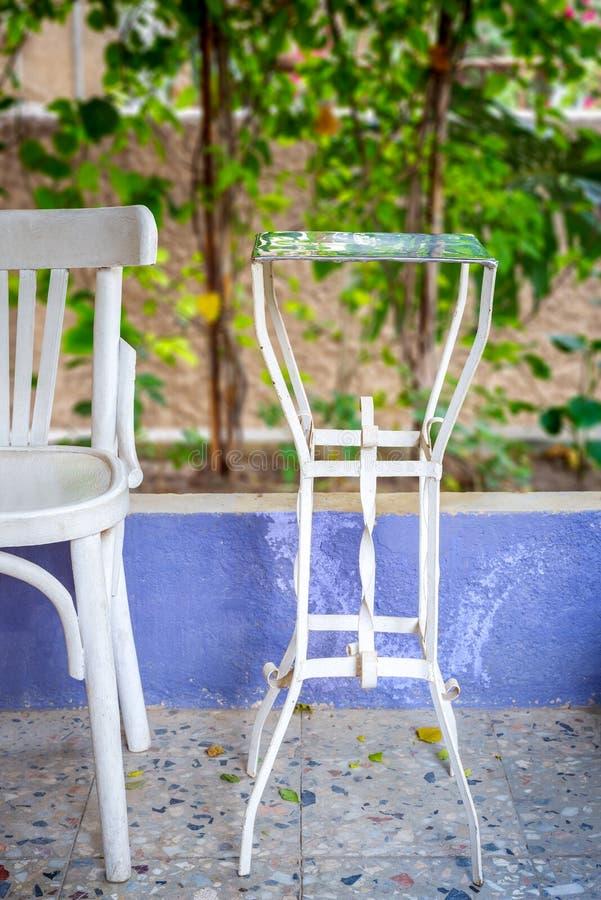 Tradycyjnego Egipskiego metalu stołu i białego herbaciany drewniany krzesło na tle zielona arywista roślina obraz royalty free