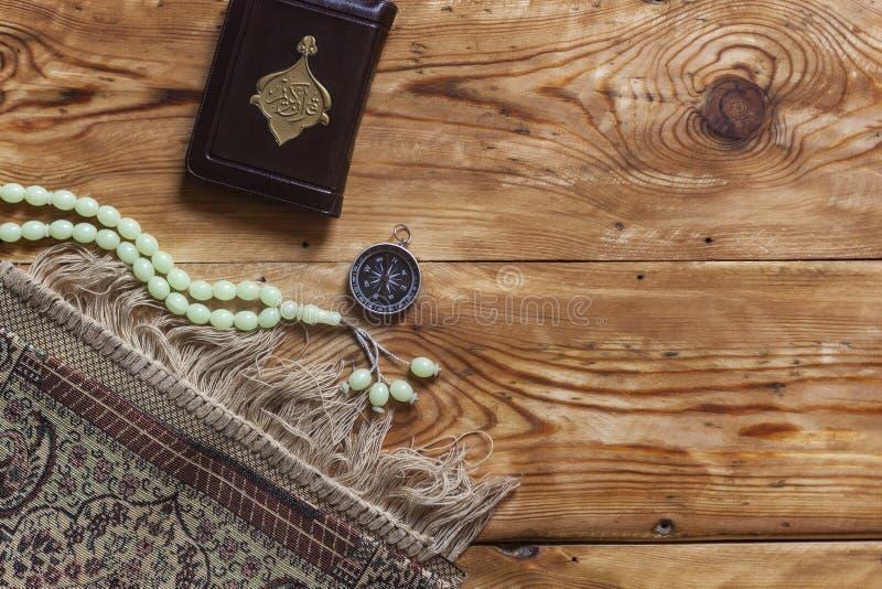 Tradycyjnej muzu?ma?skiej modlitwy ustalony plik Modlenie dywan, r??an?w koraliki, ma?a wersja ?wi?ty koran i qibla kompas na dre zdjęcie stock