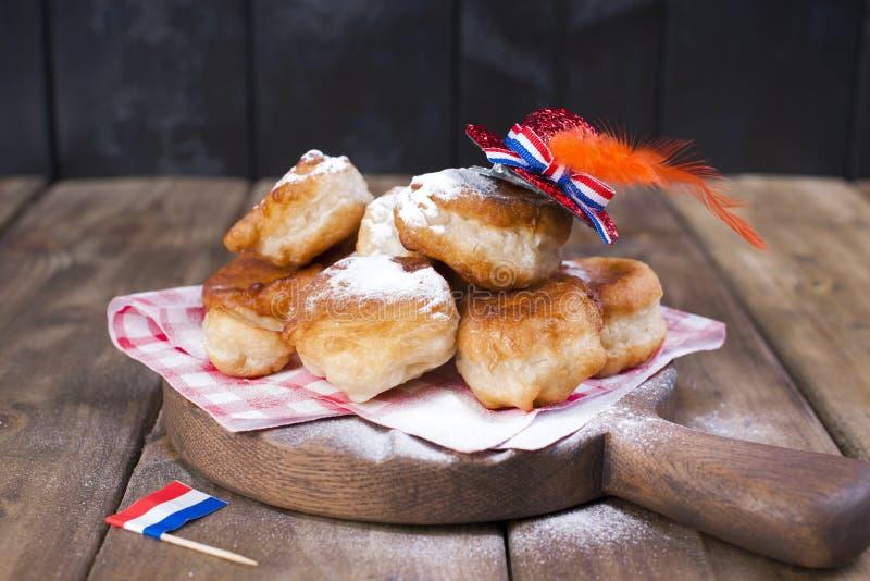 Tradycyjni Holenderscy słodcy ciasta Uczta dzień królewiątko dekoruje Pomarańczowe rzeczy dla wakacje Holandie Donuts i naczynia zdjęcia stock