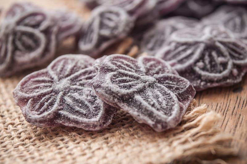 Tradycyjni purpurowi cukierki w kształtnym kwiacie na hessia obraz royalty free