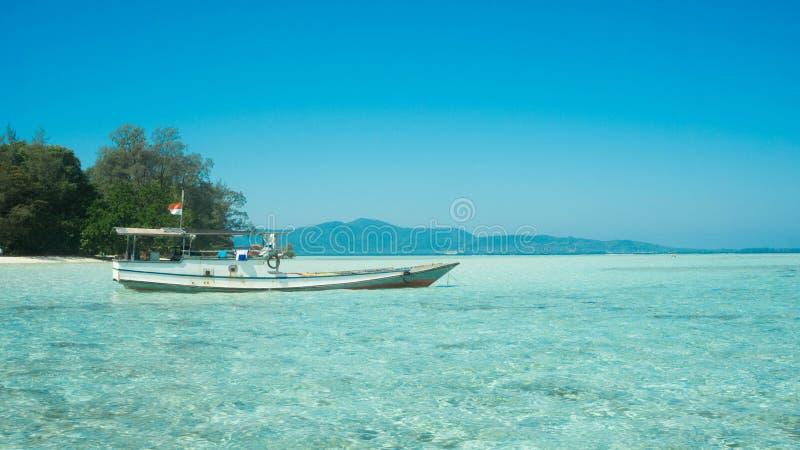 Tradycyjny łódkowaty transport na płytkim morzu z przejrzysty jasnym i wyspie w odległości zdjęcia stock