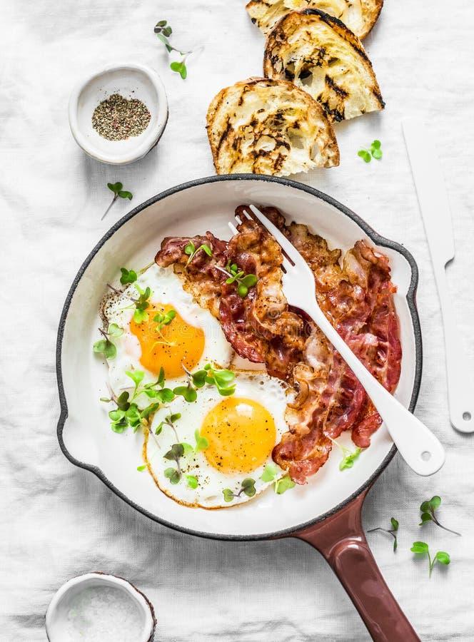 Tradycyjny śniadanie lub przekąska - smażący jajka, bekon, piec na grillu chleb na lekkim tle, odgórny widok zdjęcia royalty free