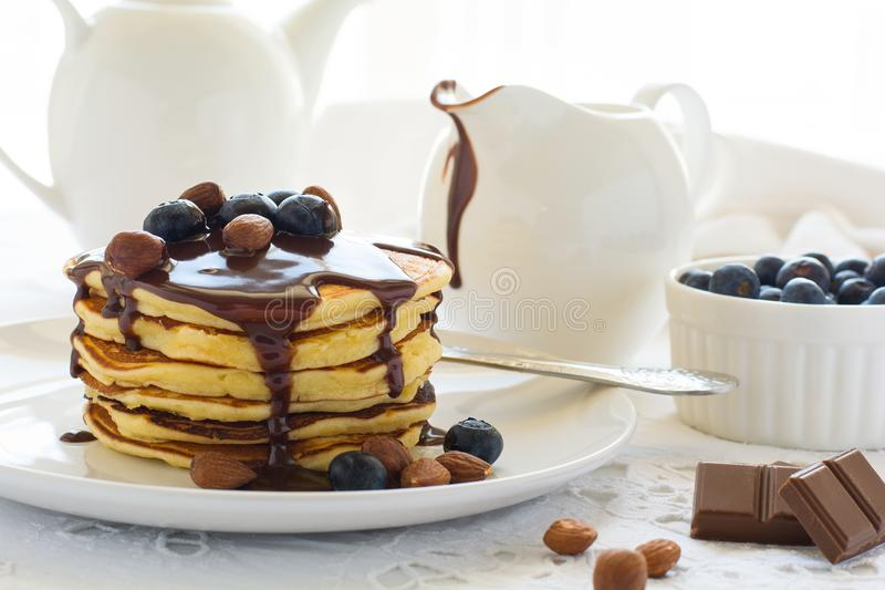 Tradycyjny śniadaniowy pojęcie Sterta bliny z czekoladowym kumberlandem, czarnymi jagodami i dokrętkami, fotografia stock