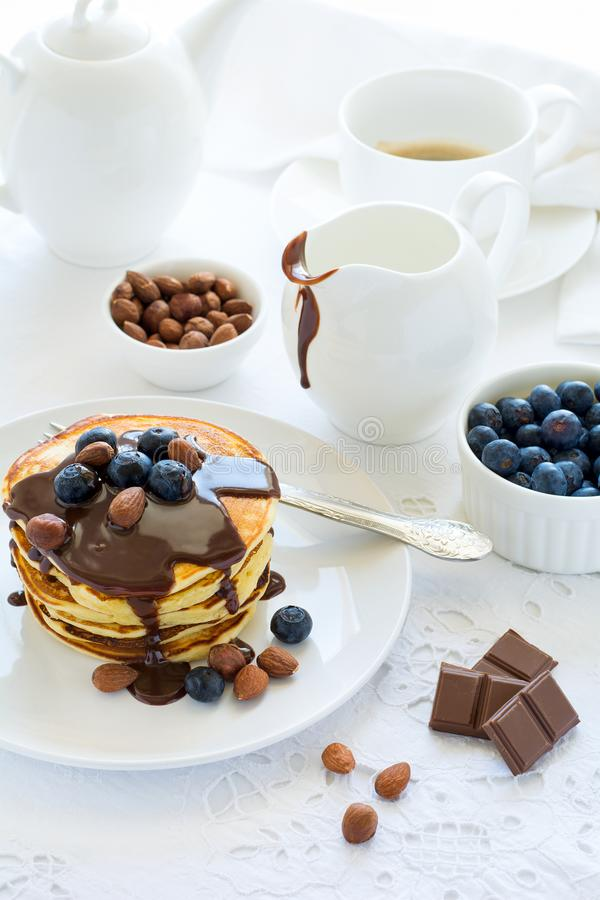 Tradycyjny śniadaniowy pojęcie Sterta bliny z czekoladowym kumberlandem, czarnymi jagodami i dokrętkami na białym stołowym płótni zdjęcie royalty free