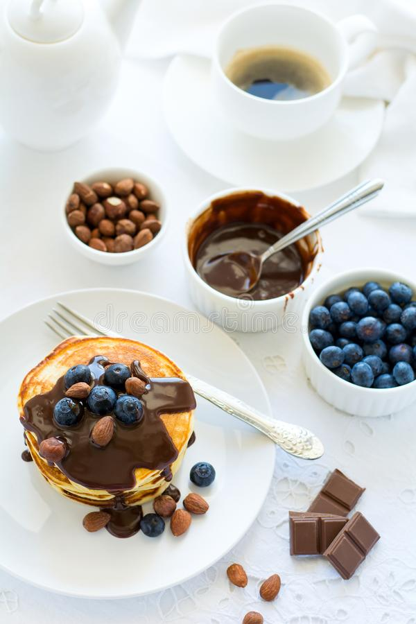 Tradycyjny śniadaniowy pojęcie Sterta bliny z czekoladowym kumberlandem, czarnymi jagodami i dokrętkami na białym stołowym płótni obrazy stock