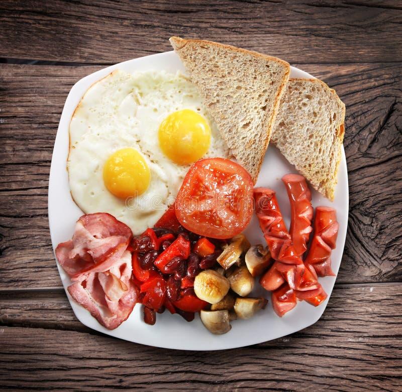 Tradycyjny Angielski śniadanie - smażący jajka, kiełbasy, becon i obrazy stock