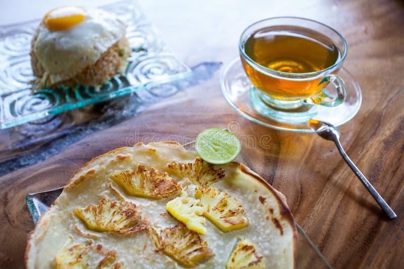 Tradycyjny Azjatycki śniadanie, ryż z jajkiem, blin z ananasem i herbata na drewnianym stole, fotografia royalty free