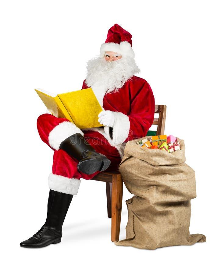 Tradycyjny czerwony biały Santa Claus czyta złotą książkę obrazy stock