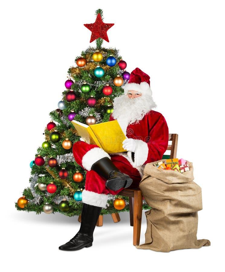 Tradycyjny czerwony biały Santa Claus czyta złotą książkę obraz royalty free