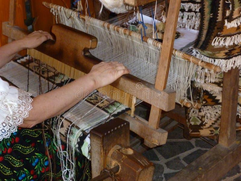 Tradycyjny drewniany krosienko robić dywanom z kobietą w traditionel ubierać w Rumunia obrazy stock