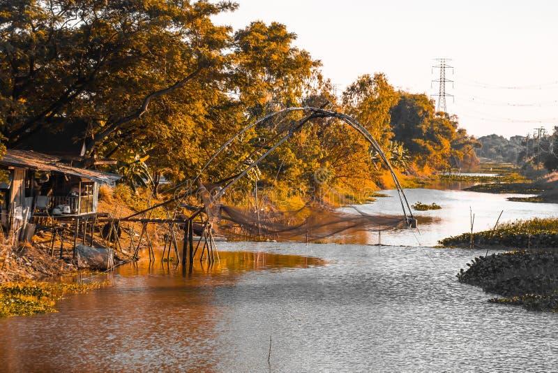 Tradycyjny drewniany t połowu oklepiec z złotym pomarańczowym pięknym lasem wzdłuż rzeki w Tajlandia tle zdjęcie stock