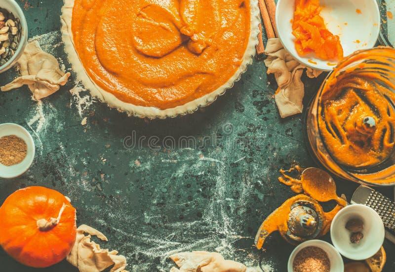 Tradycyjny dyniowego kulebiaka przygotowanie z plombowaniem, ciastem i składnikami na ciemnym nieociosanym tle, odgórny widok obrazy stock