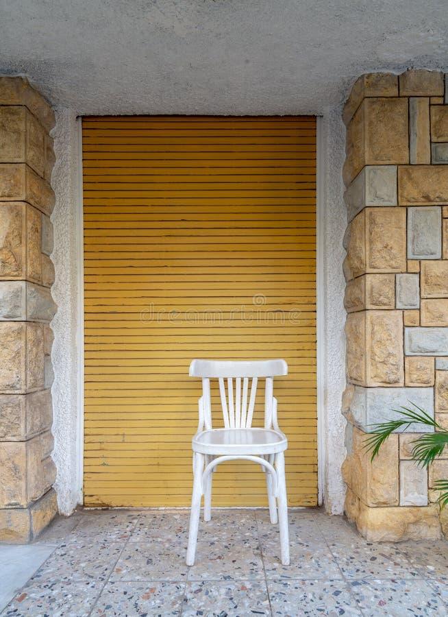 Tradycyjny Egipski biały drewniany krzesło przed cegły kamiennej ściany i kolor żółty rolki drzwi zdjęcie royalty free
