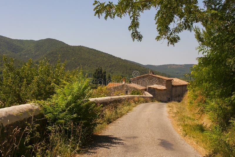 Tradycyjny francuski dom wiejski stroną droga pod podwyższonym historycznym miasteczkiem Le Poeta Laval w tDrome w Provence obraz royalty free