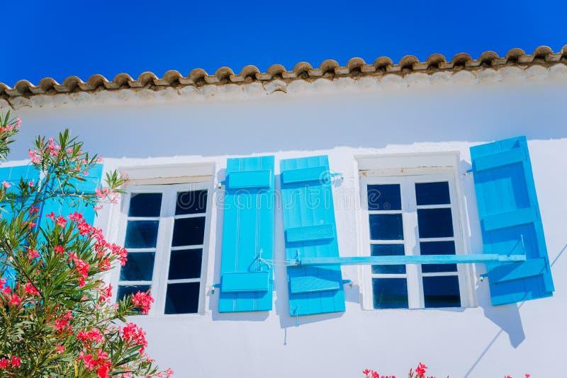 Tradycyjny grecki bielu dom z błękitnymi nadokiennymi kwiatami w Fiskardo i żaluzją, Kefalonia wyspa, Grecja obrazy royalty free