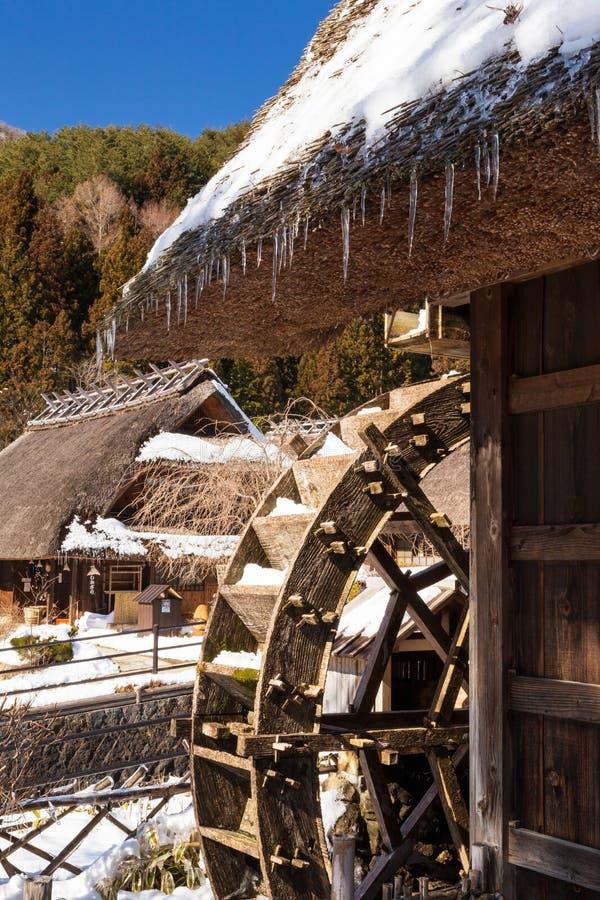 Tradycyjny Japoński wodny młyn z pokrywającym strzechą dachu domem w Sato Nenba tradycyjnej wiosce zakrywającej śniegiem w Saiko zdjęcie stock