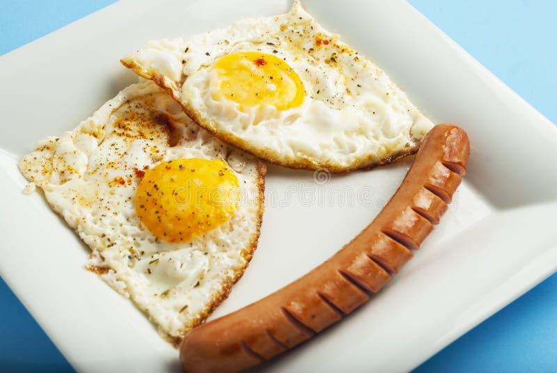 Tradycyjny Klasyczny śniadanie Smażąca kiełbasa na białego kwadrata porcelany talerzu i jajka Isoalted na Błękitnym tle fotografia stock