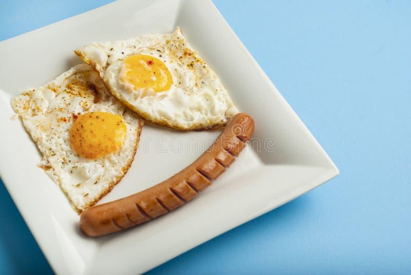 Tradycyjny Klasyczny śniadanie Smażąca kiełbasa na białego kwadrata porcelany talerzu i jajka Isoalted na Błękitnym tle obraz stock