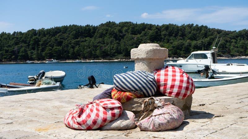 Tradycyjny Kolorowy – czerwieni, białych i błękitnych tkanina materiału pokrywy arkana sieć łowić i dok łódź w małym bruku fotografia royalty free