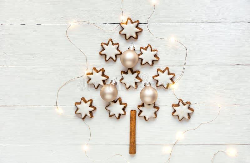 Tradycyjny Niemiecki Bożenarodzeniowy cynamon i dokrętek gwiazdy kształtujący ciastka z lodowaceniem w jedlinowym drzewie kształt obraz royalty free