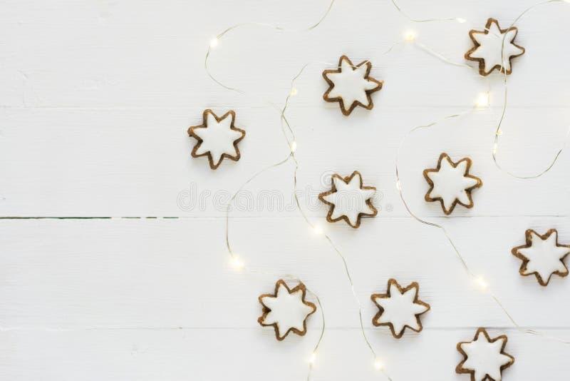 Tradycyjny Niemiecki Bożenarodzeniowy cynamon i dokrętki gwiazda kształtowaliśmy ciastka z lodowaceniem Złota girlanda zaświeca b fotografia stock