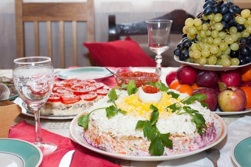 Tradycyjny Rosyjski sałatkowy śledź pod futerkowym żakietem na wielkim białym naczyniu dekorował z zieleniami i jajkami z czerwon fotografia stock