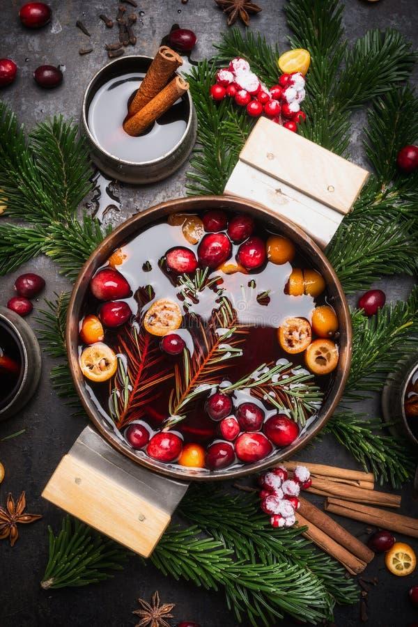 Tradycyjny rozmyślający wino w starzejącym się miedzianym kucharstwo garnku z cranberries, cynamonowi kije, pokrojona pomarańcze  fotografia stock