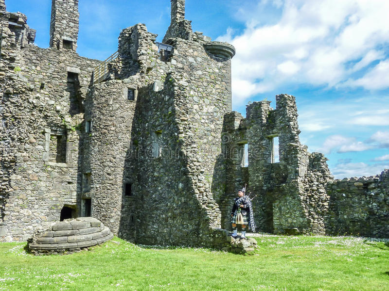 Tradycyjny szkocki bagpiper przy ruinami Kilchurn kasztel obrazy royalty free