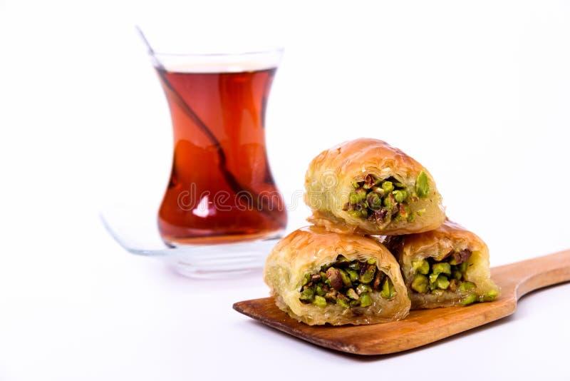 Tradycyjny Turecki deser, Baklava na drewnianym talerzu z pistacjowymi dokrętkami i Turecka herbata z łyżką na bielu, zdjęcie royalty free