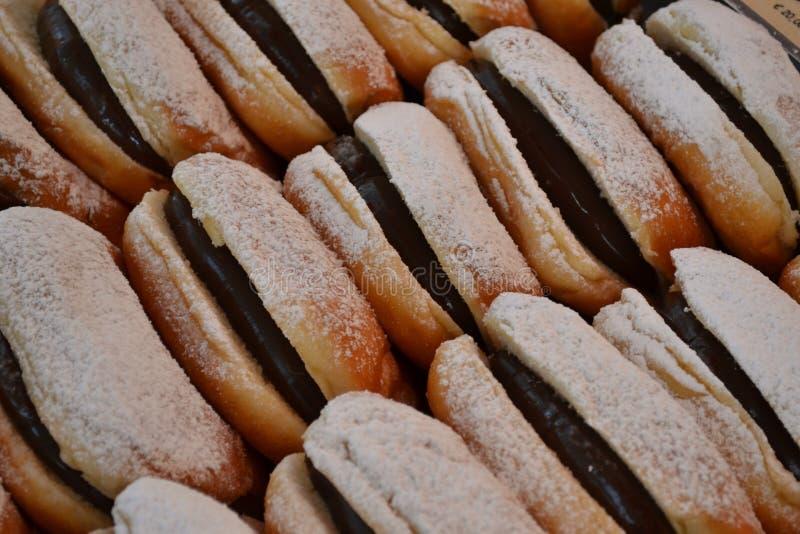 Tradycyjny Włoski ciasto dla sprzedaży w Bożenarodzeniowych kramach Mediolan - krapfen wypełniający z czekoladową śmietanką - obrazy stock