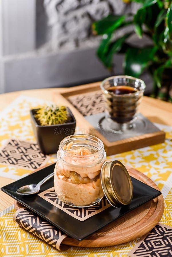 Tradycyjny Włoski deserowy tiramisu w słoju na drewnianym stole w restauracji obraz royalty free