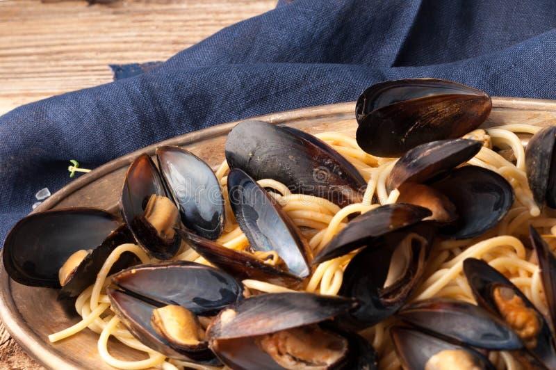 tradycyjny włoski makaron i mussels na metalu talerzu blisko błękitnej pieluchy zdjęcia stock