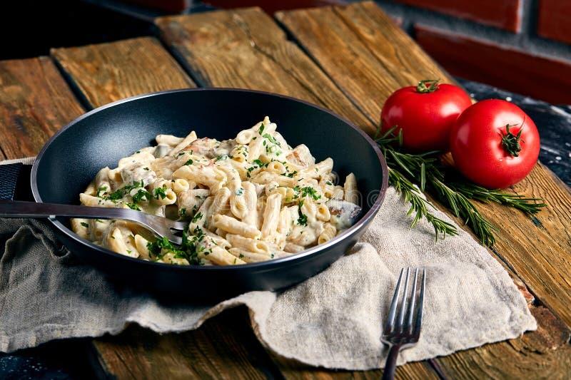 Tradycyjny w?oski naczynie spaghetti carbonara z bekonem w kremowym kumberlandzie w rynience nad ciemnym drewnianym t?em zdjęcia stock