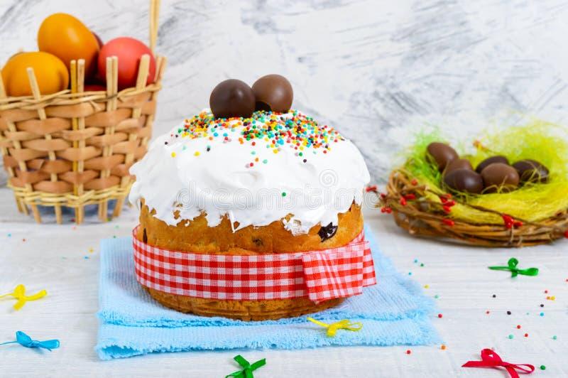 Tradycyjny wielkanoc tort kulich, czekoladowi jajka w gniazdeczku i kolorowi malujący jajka na drewnianym białym tle -, obraz stock