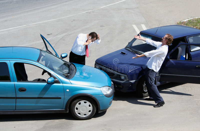 Traffic accident. One driver on the mobile phone, second expressing anger stock image