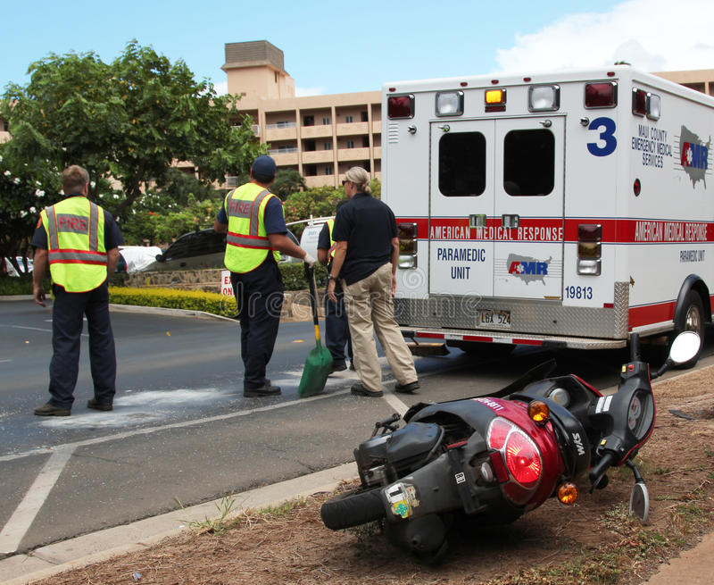Traffic accident involving a moped. JULY 26, 2012-MAUI, HAWAII: Unidentified EMT and fire responders at scene of motorscooter traffic accident. Driver survived stock photo
