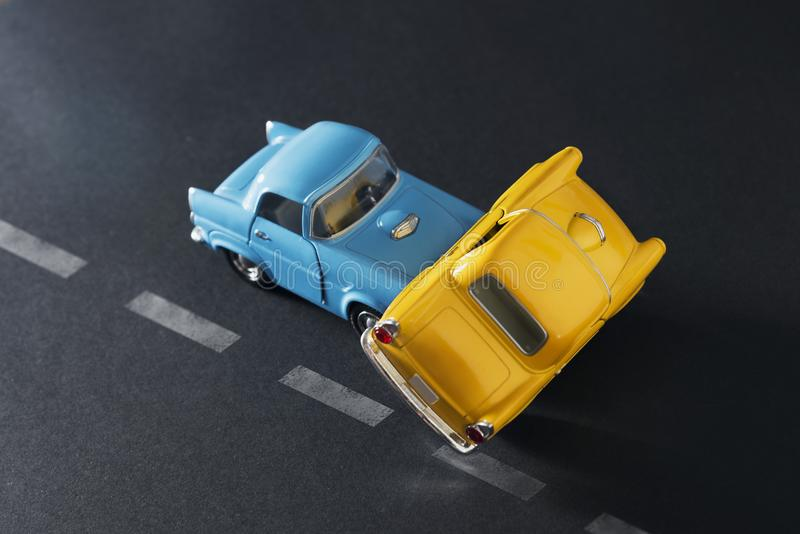 Traffic accident by toy cars. Traffic accident by two toy cars blue and yellow on a black background with road lanes stock photo