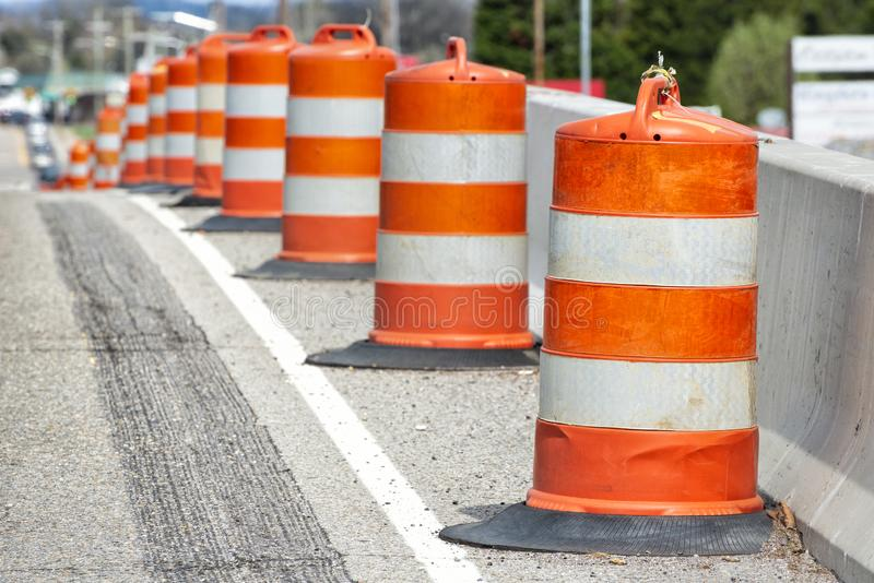 Traffic Barrels With Shallow Depth of Field. Horizontal close-up shot of orange and white striped traffic barrels down the side of a road with shallow depth of stock photo