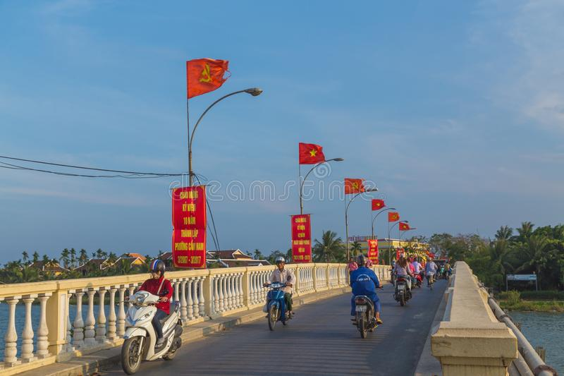 Traffic on the X bridge in Hoi An. HOI AN, VIETNAM - 24TH MARCH 2017:  People on scooters and motorbikes crossing a bridge connecting in Hoi An to Cam Nam stock image
