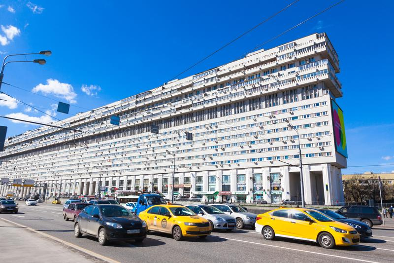 Traffic in city Moscow in Russia. Unusal 14-storey residential building is called a `home-ship` and `Titanic Built`. Buil in the style of brutalism. Yellow stock images