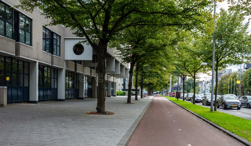 Traffic in the city, Rotterdam, Netherlands. Bike and traffic lanes, perspective view. Bike and traffic lanes, sidewalk for pedestrian with trees.Traffic in the stock image