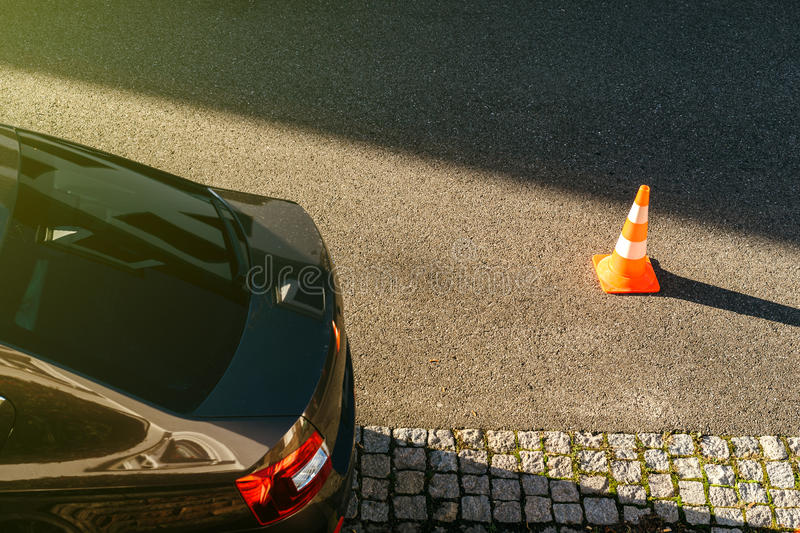 Traffic cone on asphalt near parked car - aerial drone view royalty free stock photography