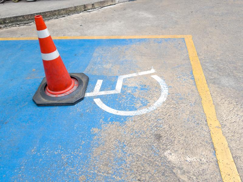 Traffic cone on Disabled parking. International Symbol of painted in bright blue on center parking space. Facilitates the provisio stock image