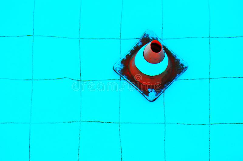 Traffic cone underwater. Plastic orange safety cone at the bottom of a swimming pool stock image
